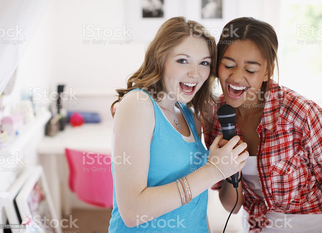Teenage girls singing into microphone stock photo