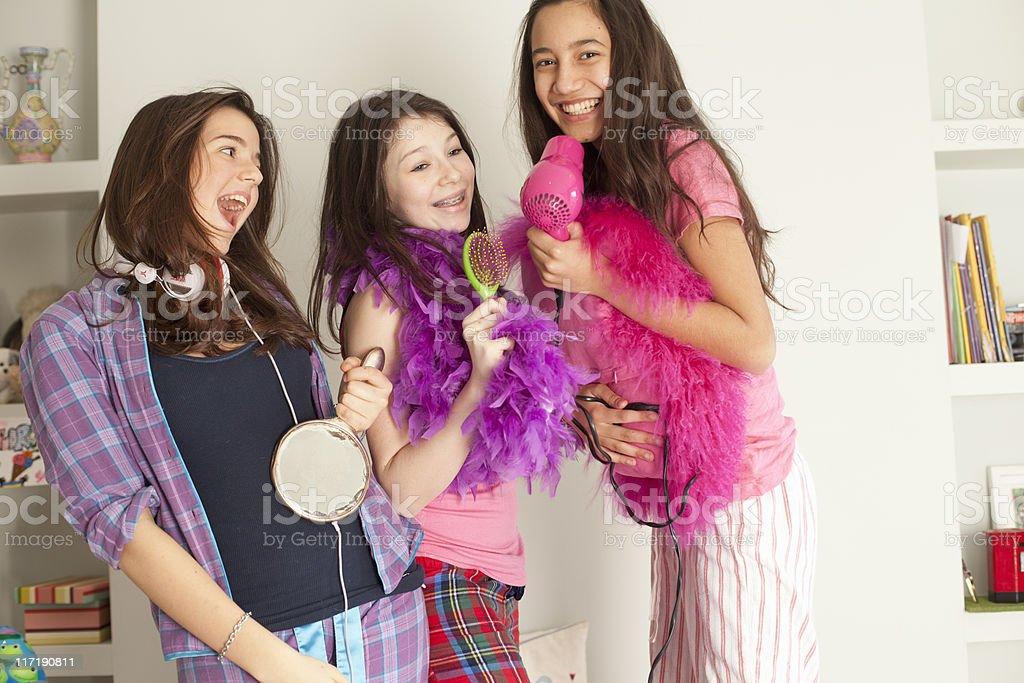 teenage girls singing , wearing pajamas stock photo
