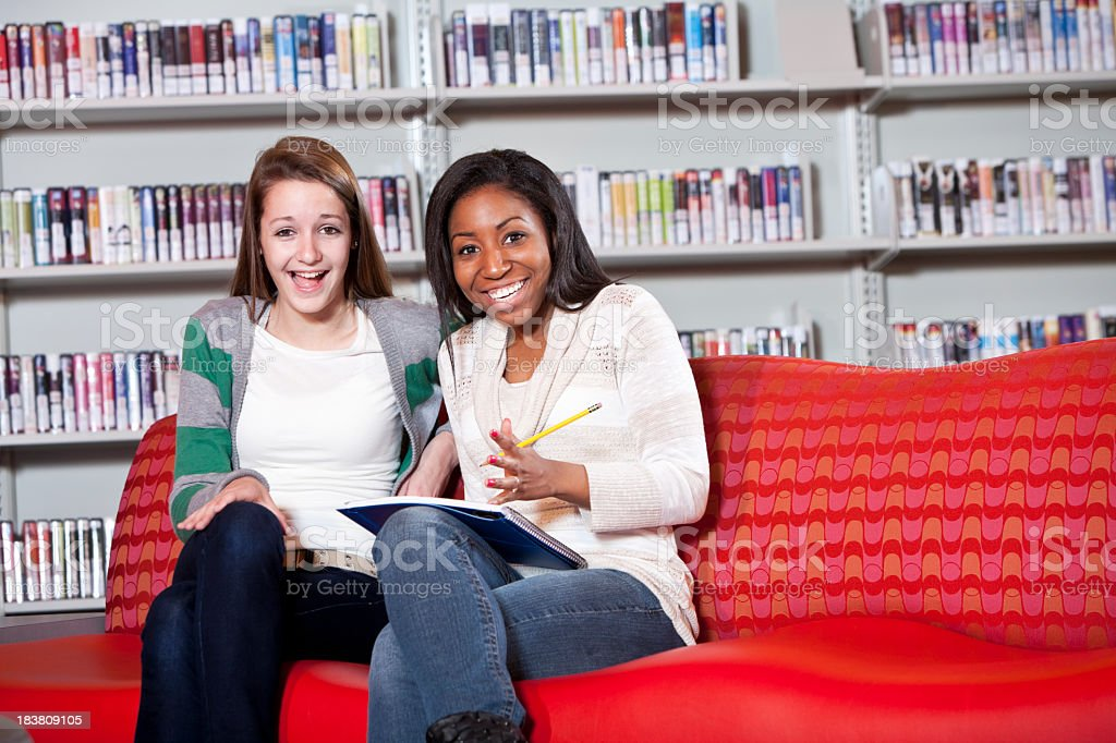 Teenage girls sitting together in school library stock photo
