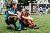 Teenage girls talking after a soccer game. Female football players are resting on soccer field. They are in sportswear.