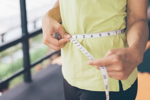 Teenage girls use their own waist measurement straps. To control the size and shape of yourself after exercise. stock photo