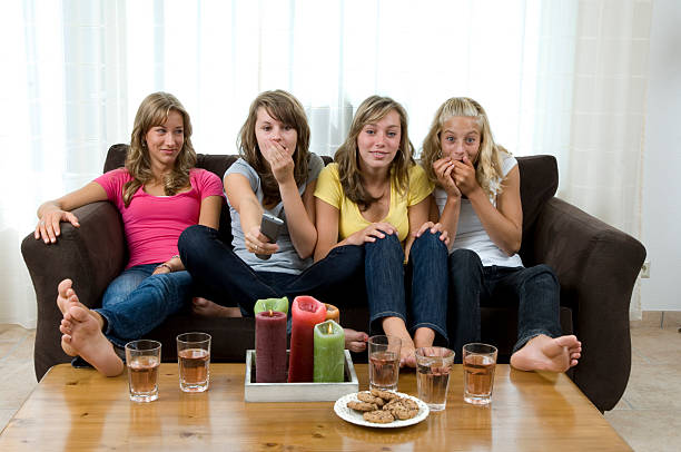 teenage girls watching tv show stock photo