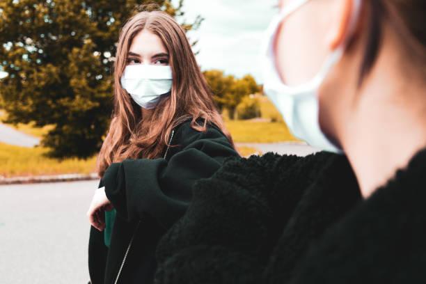 Teenage Girls Wearing Face Masks Elbow Bump Covid-19 Corona Times stock photo