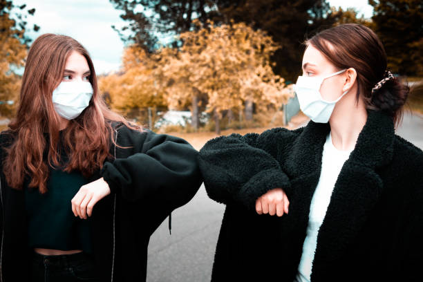 Teenage Girls Wearing Face Masks Elbow Bump Greeting Covid-19 Corona stock photo