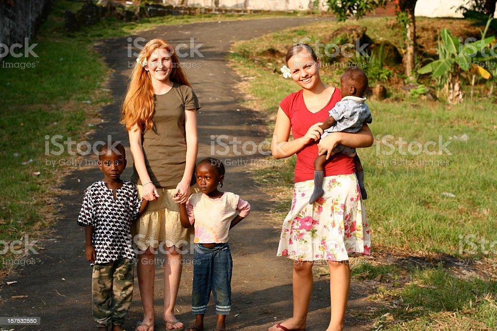 Teenage girls with African children stock photo