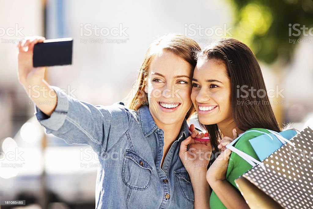 Teenage Girls With Shopping Bags Taking Self Portrait royalty-free stock photo