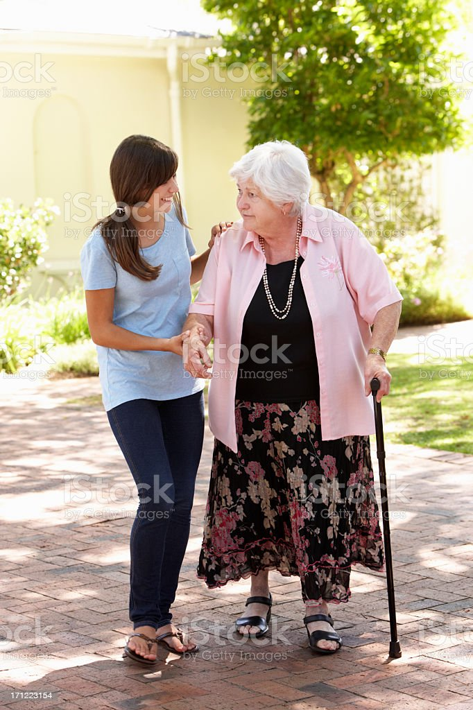 Teenage Granddaughter Helping Grandmother Out On Walk stock photo