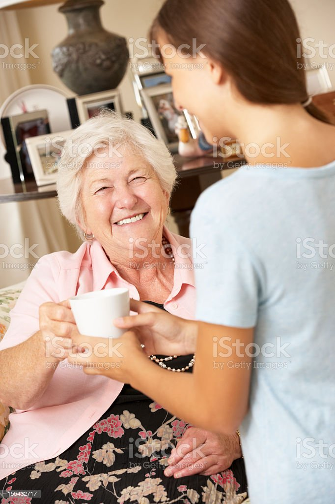 Teenage Granddaughter Making Grandmother Hot Drink At Home royalty-free stock photo