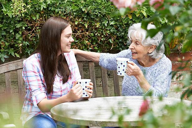 Teenager entspannend mit Großmutter Enkelin im Garten – Foto