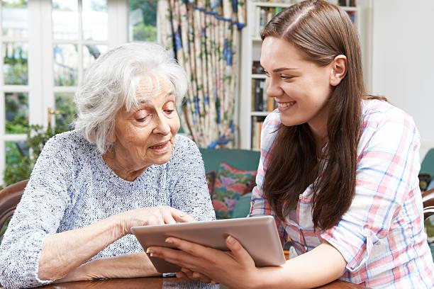 Teenage Enkelin mit Großmutter verwenden digitale