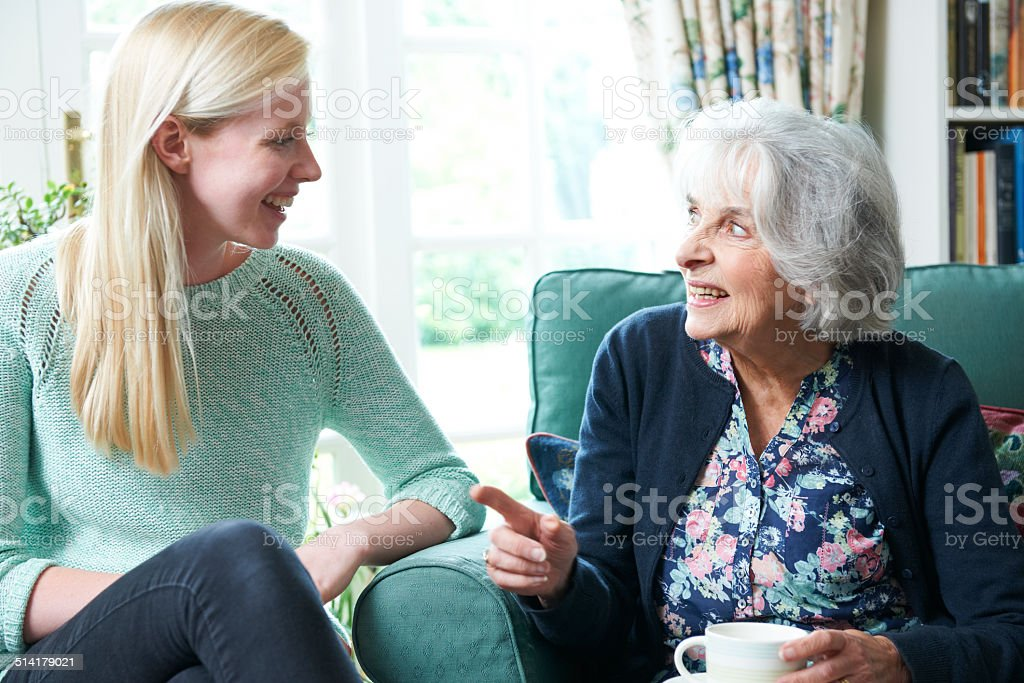 Teenage Granddaughter Visiting Grandmother stock photo