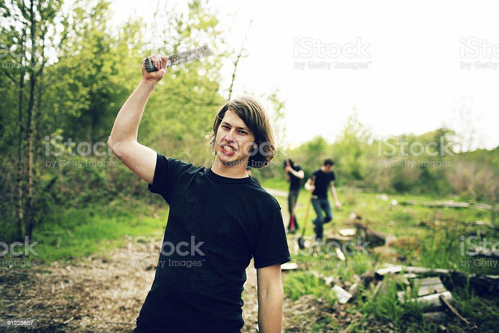 Teenage Guy Wielding Machete Over Head royalty-free stock photo