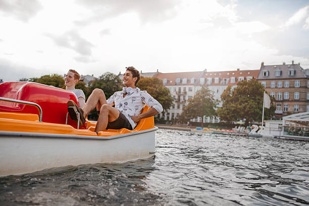 teenage guys enjoying boating in the lake - pédalo photos et images de collection