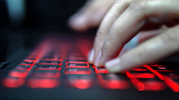 Teenage Hacker Girl Attacks Corporate Servers in Dark, Typing on Red Lit Laptop Keyboard. Room is Dark Teenage Hacker Girl Attacks Corporate Servers in Dark, Typing on Red Lit Laptop Keyboard. Room is Dark computer crime stock pictures, royalty-free photos & images