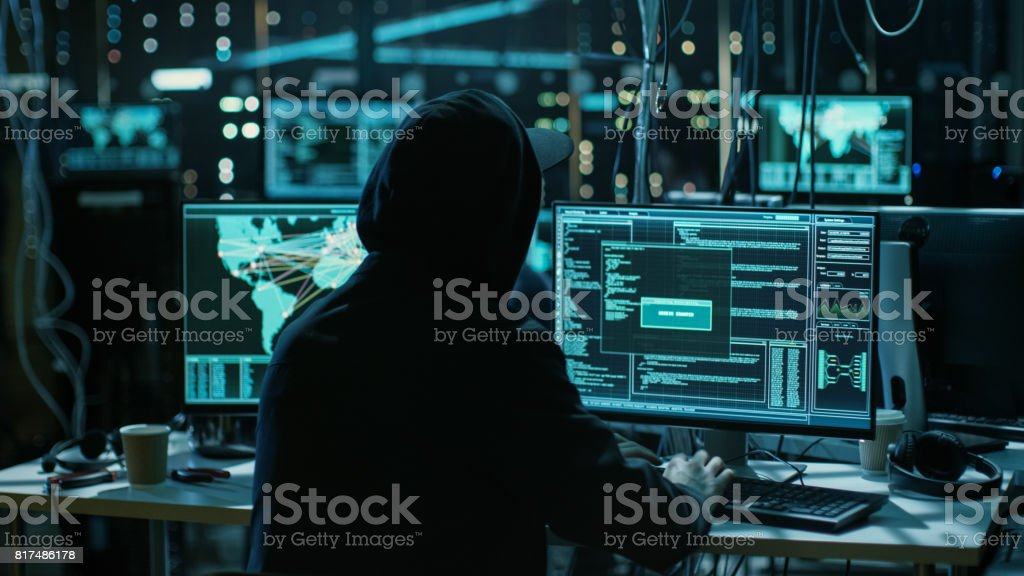 Teenage Hacker Working with His Computer Infecting Servers and Infrastructure with Malware. His Hideout is Dark, Neon Lit and Has Multiple displays. stock photo