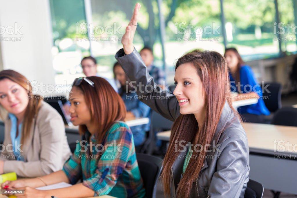 Teenage high school girl raising hand during class stock photo