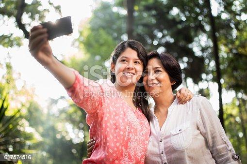 istock Teenage latin girl taking selfie with her mother 617574516