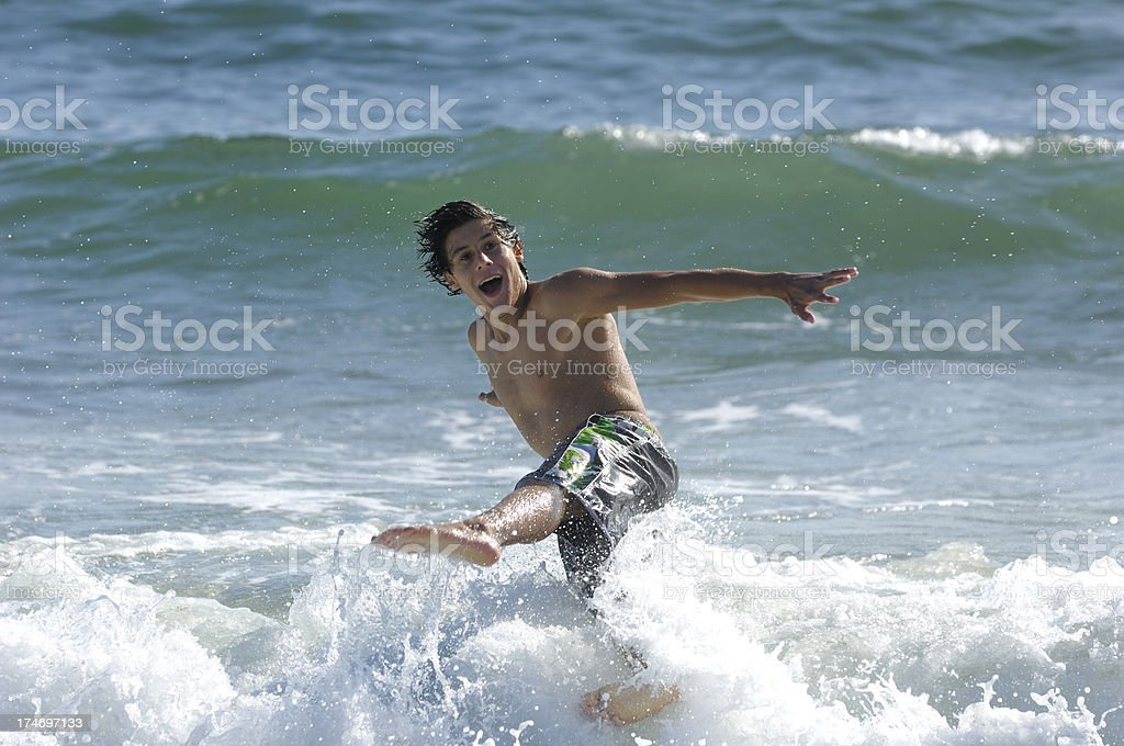 Teenage Latino Boy Knocked Off His Feet by Ocean Wave royalty-free stock photo