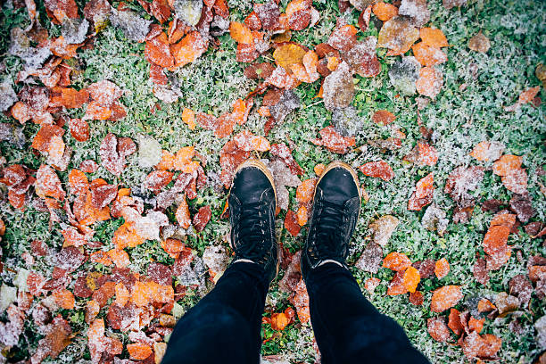 Teenage legs in boots on fallen leaves and snow – Foto
