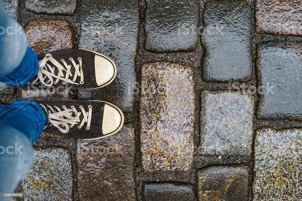 Teenage legs in sneakers on wet pavement – Foto