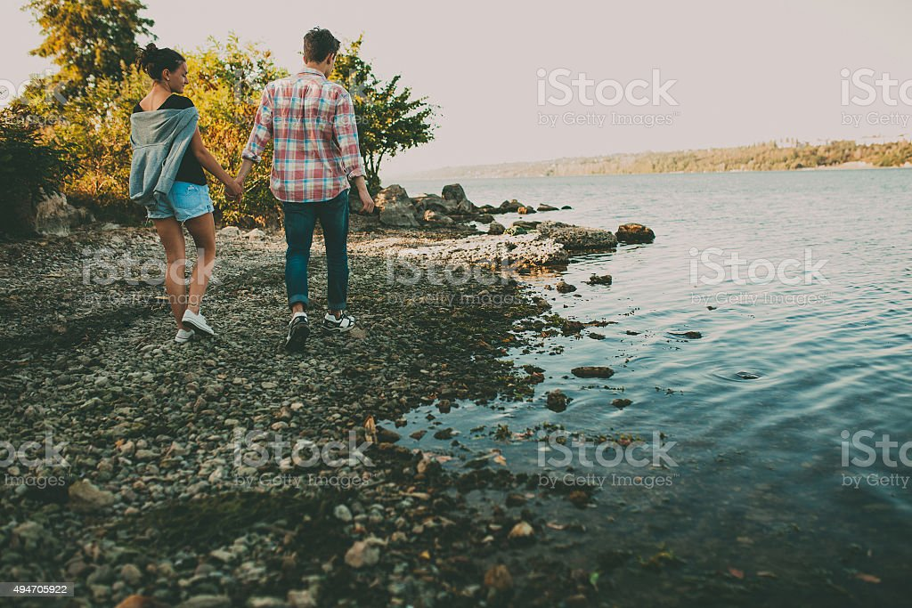 Teenage loving couple walking together by a lake stock photo