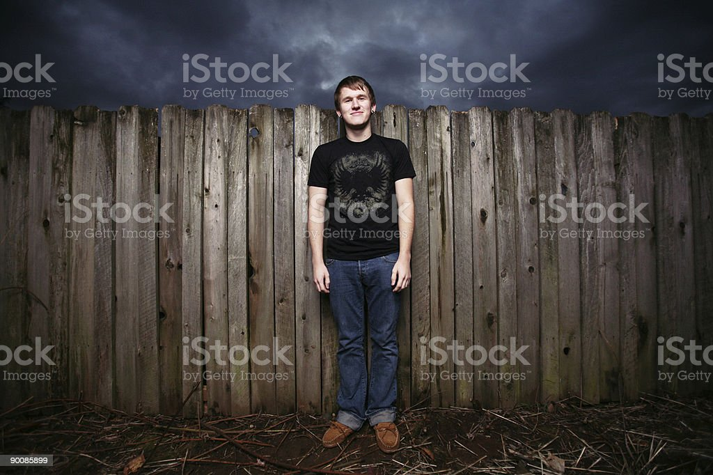 Teenage Male Standing by a Fence royalty-free stock photo
