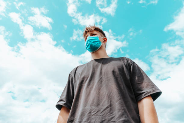 Teenage Man with Protective Corona Covid-19 Face Mask against Summer Sky stock photo