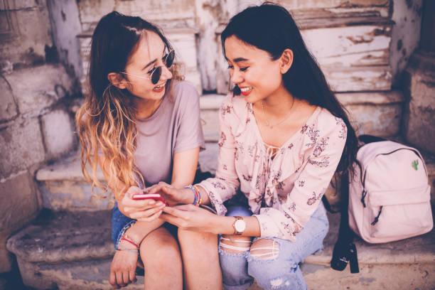 teenager multiethnischen hipster mädchen smartphone-bildschirm betrachten und lachen - happy weekend bilder stock-fotos und bilder