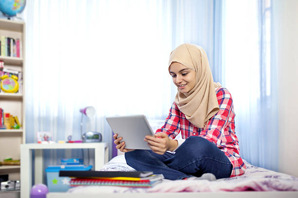 teenage muslim girl using tablet computer - arabic girl stock photos and pictures