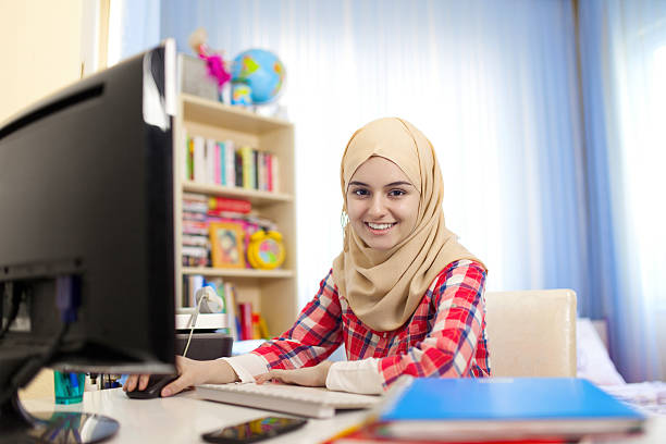 teenage muslim girl working at home - arabic girl stock photos and pictures