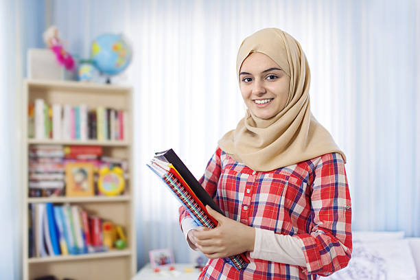 teenage muslim student girl standing at home - arabic girl stock photos and pictures