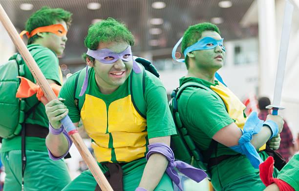 teenager mutant ninja schildkröten cosplayers - cartoon kostüme stock-fotos und bilder