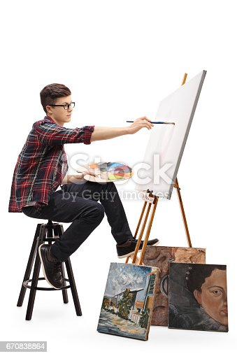 istock Teenage painter painting on a canvas with a paintbrush 670838864