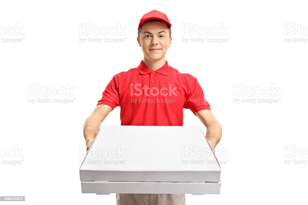 Teenage pizza delivery boy giving pizza boxes stock photo