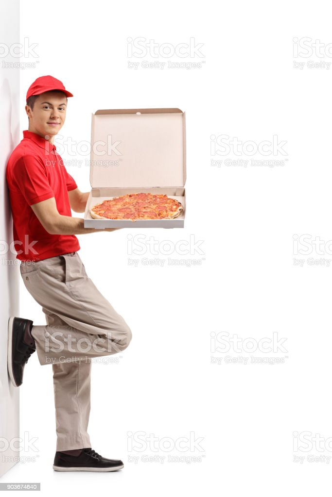 Teenage pizza delivery boy leaning against a wall stock photo