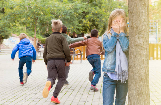 Teenage playing hide-and-go-seek in the playground stock photo