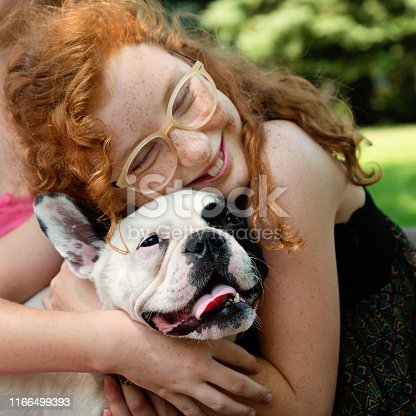Cute teenage girl having leisure time in a public park in summer with a dog. She has red hair, freckles and glasses. Dog is a young french bulldog. Square head and shoulder outdoors shot with copy space.