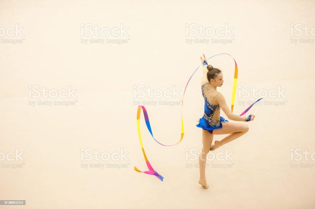 Teenage Rhythmic Gymnastics Athlete Practicing with Ribbon.