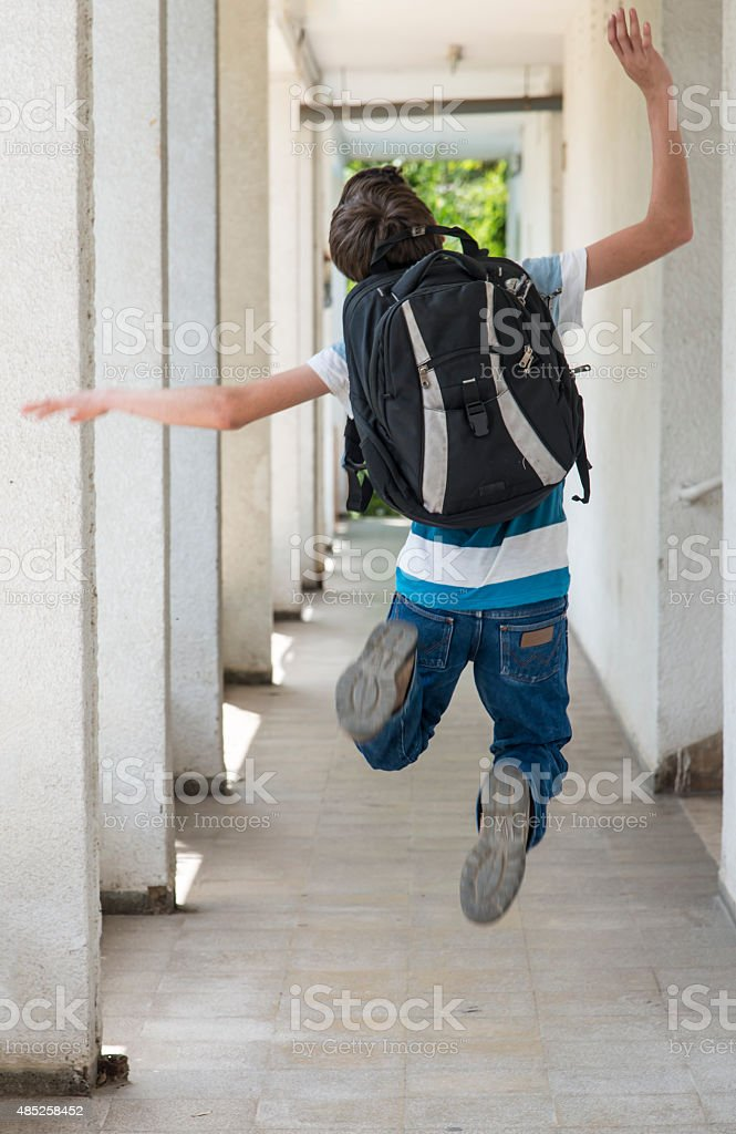 Teenage school boy with a backpack jumping to school stock photo