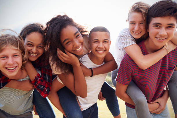 Teenage school friends having fun piggybacking outdoors stock photo