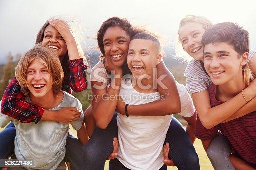 istock Teenage school friends having fun piggybacking outdoors 826221430