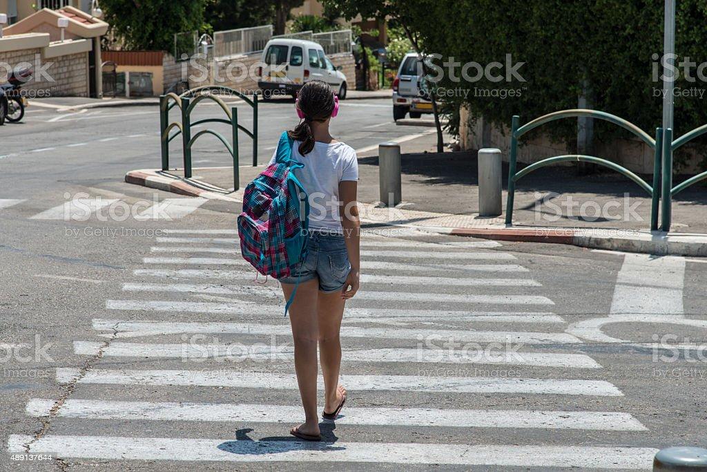 Teenage school girl with a backpack and headphones stock photo