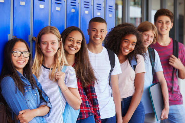 Teenage school kids smiling to camera in school corridor stock photo