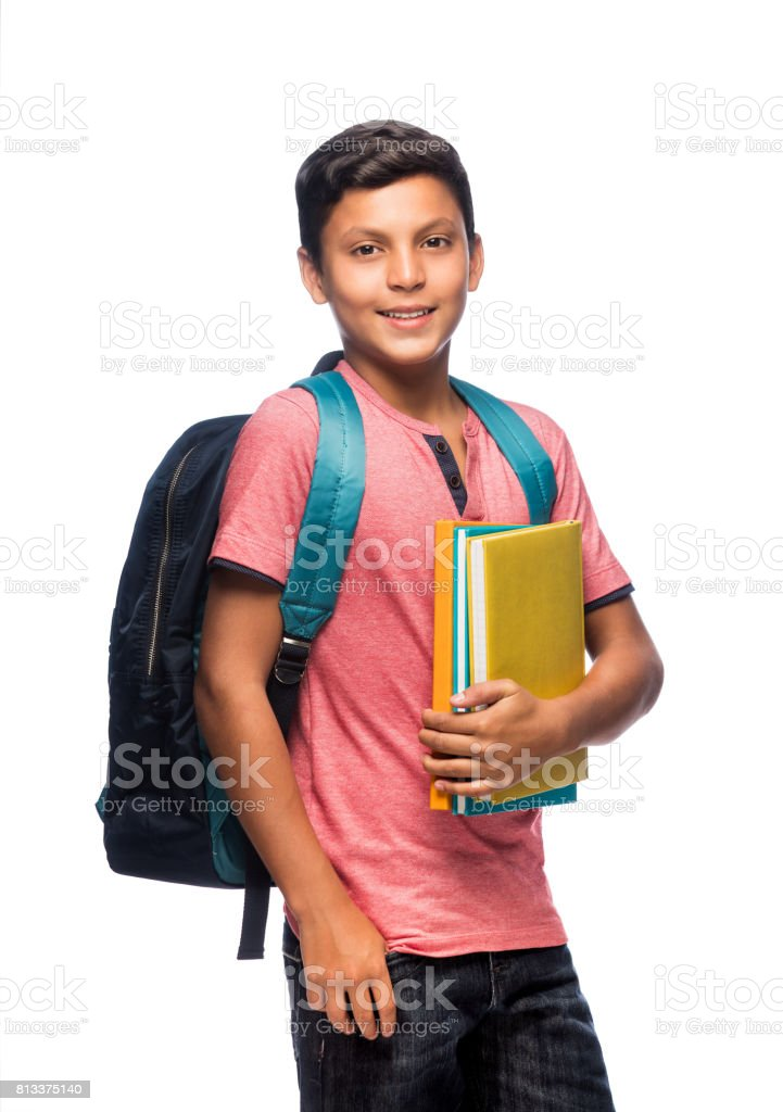 Teenage schoolboy standing with books and smiling stock photo