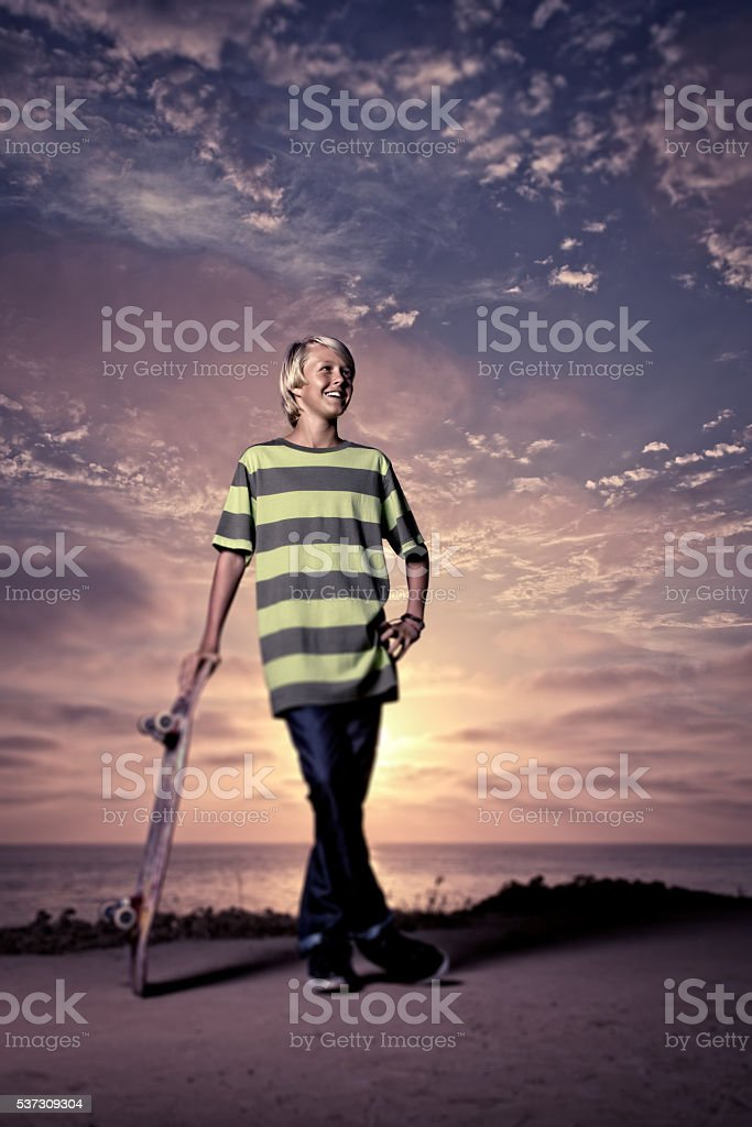Teenage Skateboarder at Sunset by the Beach stock photo