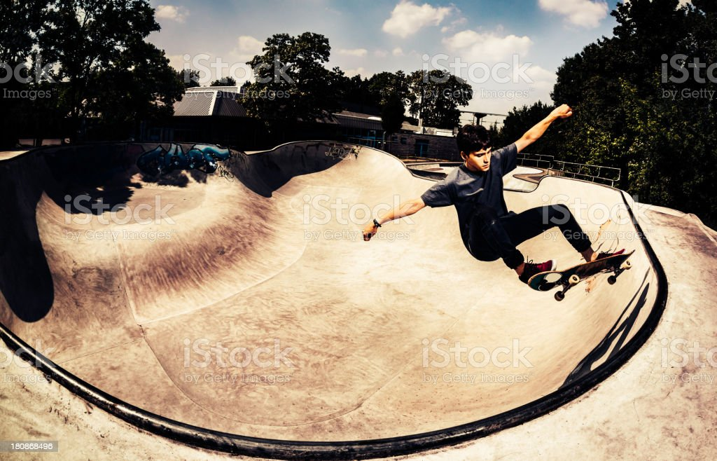 Teenage skateboarder performing a trick stock photo