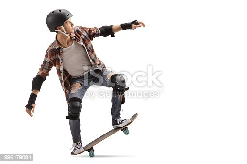 Full length profile shot of a teenage skater performing a manual isolated on white background
