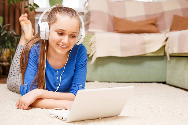 Teenage smiling girl using laptop on the floor Teenage smiling blonde girl with white headphones using laptop on the floor. Smiling teenager with laptop at home. On-line education background sergionicr stock pictures, royalty-free photos & images