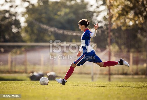 Teenage girl running with soccer ball on a playing field and about to kick the ball.