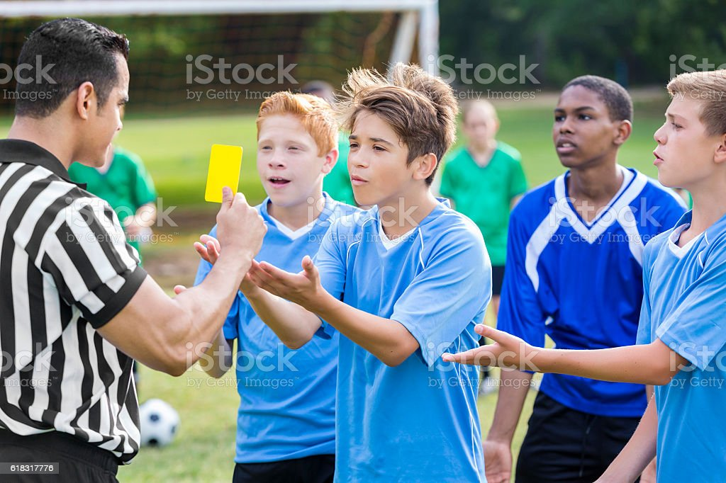 Teenage soccer player argues with referee stock photo